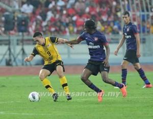 Pemain Malaysia, Norshahrul Idlan Talaha diasak pemain Arsenal pada perlawanan persahabatan di Stadium Nasional Bukit Jalil, malam tadi. - UTUSAN/AHMAD ZAKKI JILAN